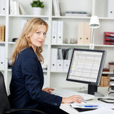 Mid Adult Businesswoman Using Computer At Desk Stock Image