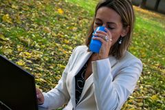 Businesswoman using laptop on coffee break in nature. royalty free stock image