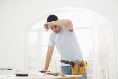 Mid-adult carpenter wiping his brow in new house Royalty Free Stock Photo