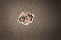 Mid adult Caucasian man looking away from ripped paper hole Stock Photo