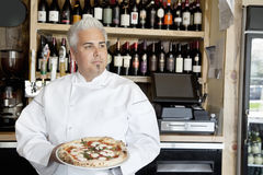 Mid adult chef holding pizza while looking away Royalty Free Stock Image