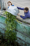 A mid-adult couple disposing of garden waste in a recycling centre Royalty Free Stock Image