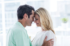 Mid adult couple embracing at home Royalty Free Stock Photography