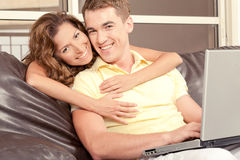Mid adult couple with laptop. Smiling mid-adult couple opearting laptop and looking at camera royalty free stock images