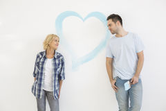 Mid-adult couple looking at each other with painted heart on wall Stock Photo