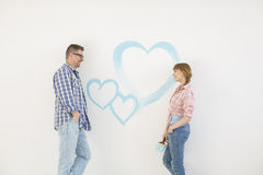 Mid-adult couple looking at each other with painted heart on wall Royalty Free Stock Images