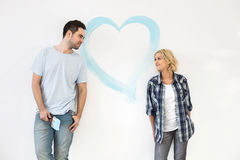 Mid-adult couple looking at each other with painted heart on wall stock images