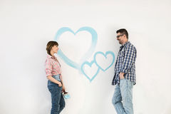 Mid-adult couple looking at each other with painted heart on wall royalty free stock photography