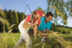 Mid adult couple searching a golf ball in bush.  Royalty Free Stock Images