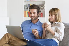 Mid adult couple shopping using laptop and credit card in modern apartment. Young men and women buying something online at home Royalty Free Stock Photo