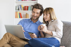 Mid adult couple shopping using laptop and credit card in modern. Young men and women buying something online at home with portable computer Stock Image
