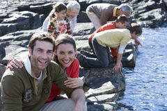 Mid adult couple sitting on rock, family in background Stock Photography