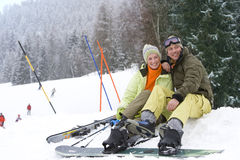 Mid adult couple sitting in snow on ski vacation Stock Image