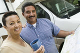 Mid-adult couple standing beside caravan and looking at camera Royalty Free Stock Images