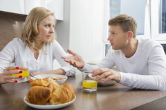 Mid adult couple talking while having breakfast at home Royalty Free Stock Photos
