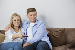 Mid adult couple watching television on sofa Stock Images