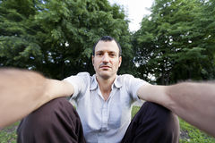 Self Photography at the Park. Mid adult (early 30's) caucasian man looking at the camera with an enigmatic confident gaze photographing himself at the park royalty free stock photos