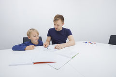 Mid adult father assisting boy in studies Stock Images