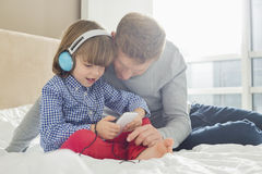 Mid adult father with boy listening music on headphones in bedroom Royalty Free Stock Images