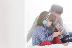 Mid adult father with boy listening music on headphones in bedroom Stock Photos