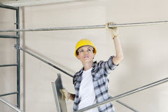 Mid adult female architect looking up while standing under scaffold at construction site Stock Photography