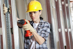 Mid adult female contractor drilling at construction site Royalty Free Stock Photography