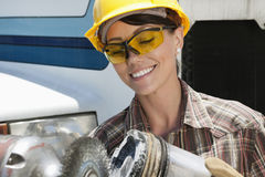 Mid adult female industrial worker buffing a truck engine cylinder Royalty Free Stock Photography