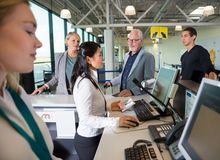 Staff Checking Passport On Computer While Passengers Waiting In Royalty Free Stock Photos