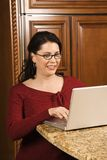 Mid-adult female working on computer. Caucasian woman typing on laptop in kitchen and smiling Stock Photos