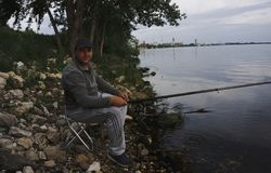 Mid adult fisherman on holiday on river, relaxing and fishing . stock photo