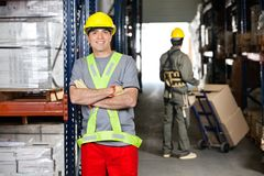 Mid Adult Foreman With Arms Crossed At Warehouse Stock Photos