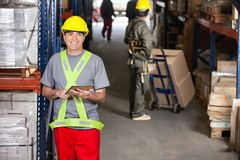Mid Adult Foreman With Digital Tablet At Warehouse. Portrait of happy mid adult foreman with digital tablet and coworker pushing handtruck at warehouse Royalty Free Stock Photography