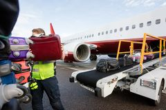 Ground Member Stacking Bags On Trailer At Runway. Mid adult ground member stacking bags on trailer at runway royalty free stock photography