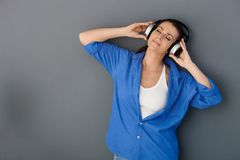 Mid-adult happy woman with headphones. Portrait of attractive mid-adult happy woman listening to music with headphones, eyes closed, daydreaming, smiling Stock Photography