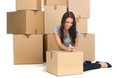 Mid adult happy woman during move with boxes at new flat. Young woman writing on boxes and smiling while moving to new apartment Stock Photos
