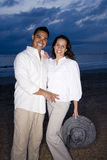 Mid-adult Hispanic couple smiling on beach at dawn. Happy mid-adult Hispanic couple smiling on beach at dawn stock photos