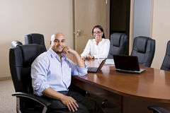 Mid-adult Hispanic office workers in boardroom Royalty Free Stock Images