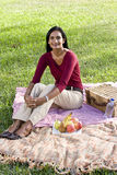 Mid-adult Indian woman sitting on picnic blanket Stock Photos