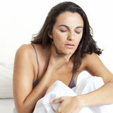 Mid-adult latin sitting in bed sick Stock Image
