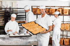 Mid Adult Male Baker Showing Baked Breads In Bakery Stock Photography