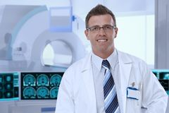 Mid-adult male doctor in MRI room at hospital stock images