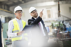Mid adult male supervisors having discussion in metal industry Royalty Free Stock Photography