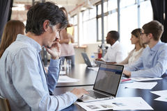 Mid adult male using laptop at a business meeting Stock Photography