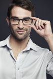 Mid adult man adjusting glasses Royalty Free Stock Photos