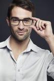 Mid adult man adjusting glasses Royalty Free Stock Photos