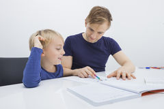 Mid adult man assisting boy in studies at table Royalty Free Stock Image
