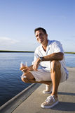 Mid-adult man on dock by water enjoying drink. On sunny day Royalty Free Stock Photo