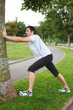 Mid adult man doing stretching exercises using a tree. Attractive mid adult spotrsman doing stretching exercises outdoors using a tree Stock Photo