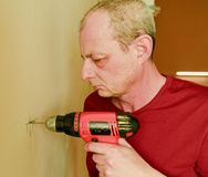 Mid-adult man drilling hole in wall. Closeup concept. Mid-adult man drilling hole in the wall. Closeup concept Stock Photography