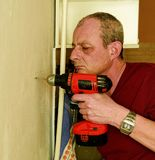 Mid-adult man drilling hole in the wall. Closeup concept. Mid-adult man drilling hole in the wall. Closeup concept Royalty Free Stock Images